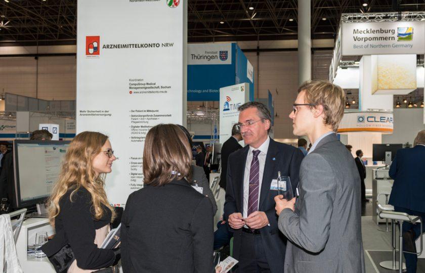 Frank Ladendorf (2. v. r.), Projektleiter von Arzneimittelkonto.NRW und Geschäftsführer der CompuGroup Medical Managementgesellschaft mbH, informiert Standbesucher zum Projekt.